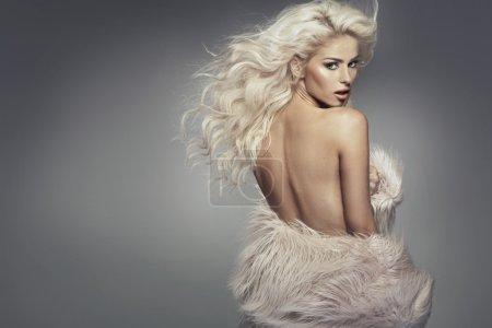 Nude girl wearing the fur coat