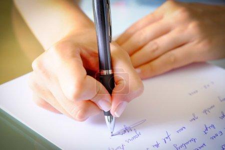 Photo pour Fille écrit une lettre sur une feuille de papier avec un stylo noir blanc. - image libre de droit