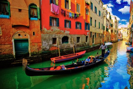 Photo for Gondolas along canal  in Venice Italy and blue water - Royalty Free Image