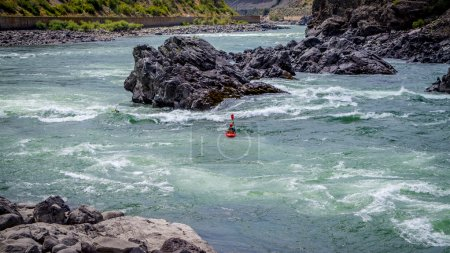 Kayakers navigating through the White Water Rapids and around Rocks
