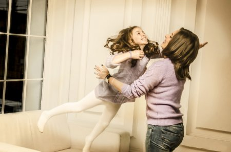 Little girl jumping on her mother hands