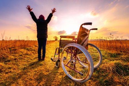 Photo pour Miracle récupération : jeune fille se lève de fauteuil roulant et lève les mains vers le haut. Ravi jeune fille debout d'un fauteuil roulant à l'extérieur. Tourné dans la prairie. Concept de récupération - image libre de droit