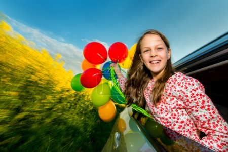 Photo for Laughing long-haired little girl with colourful balloons in a moving car - yellow flowers background - Royalty Free Image