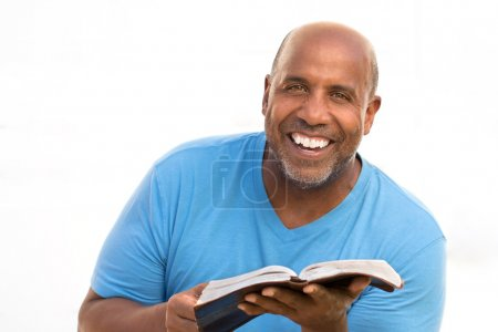 Photo for African American man smiling and reading - Royalty Free Image