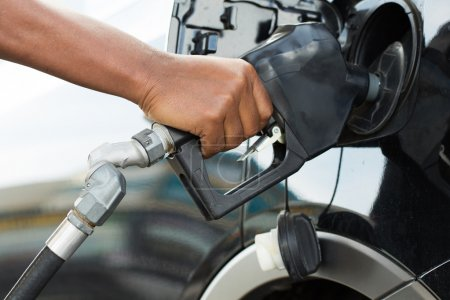 A man's hand filling up a car with gas or petrol a...