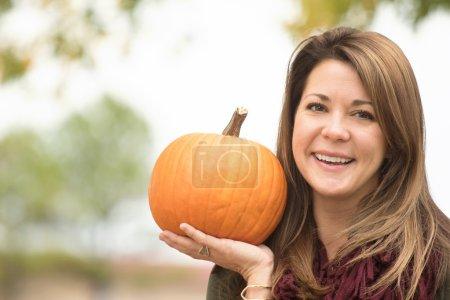 Woman holding a pumpkin