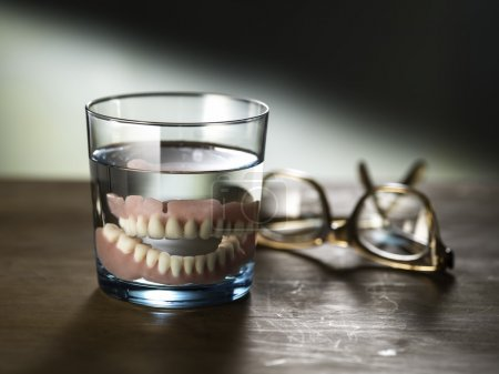 Still life photography of dentures in a glass of w...