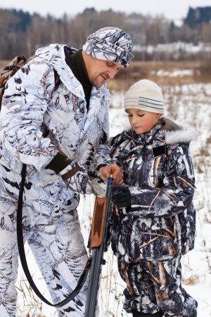 cazador muestra a su hijo cómo cargar la pistola deportiva