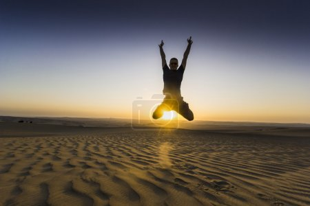 jumping man with hands up at sunset in desert