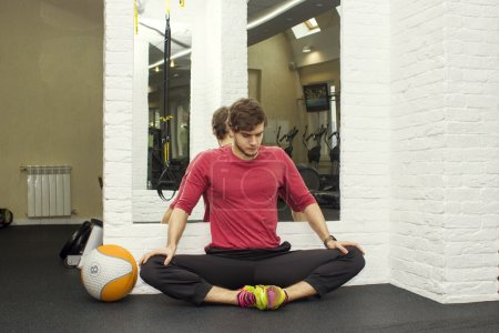 Fitness athletic trainer shows exercises with foarm roll, ball in gym.