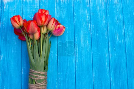 Colorful tulips on cyan wooden table. Top view with copy space