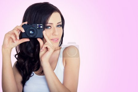 young woman with a vintage camera. pink background