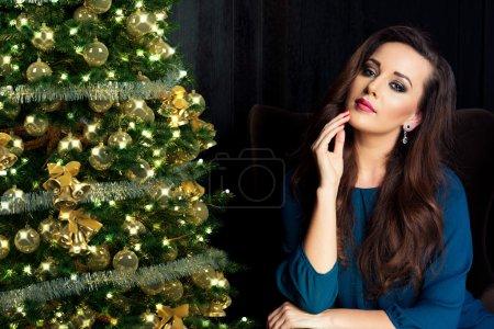 Photo pour Personnes, vacances et concept glamour - femme souriante en robe de soirée sur fond de lumières arbre de Noël - image libre de droit