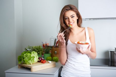 woman is eating a salat in bowl