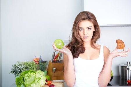 Photo for Diet. Dieting concept. Healthy Food. Beautiful Young Woman choosing between Fruits and Sweets - Royalty Free Image