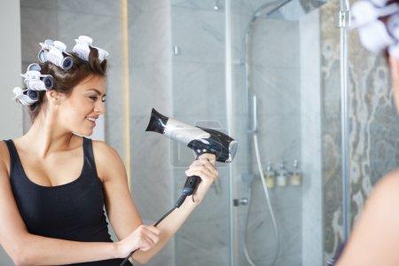 Photo pour Jeune femme de mettre des bigoudis dans les cheveux - image libre de droit