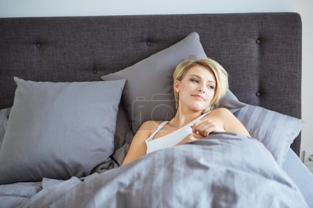 woman resting in bed with hands beside her head