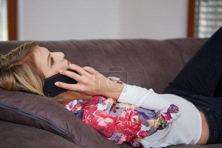 Attractive woman sitting on cosy couch in bright living room having a phone call