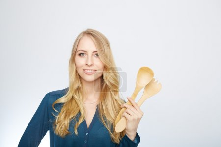 Young woman holding a wooden spoon, isolated.