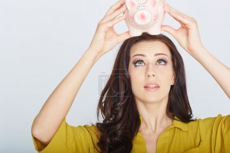 woman looks into a piggy bank
