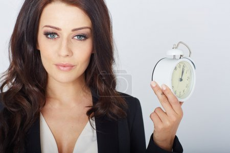 Photo pour Young businesswoman with an alarm clock. In white studio - image libre de droit