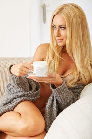 Photo for Smiling woman holding a cup of coffee in her living room - Royalty Free Image