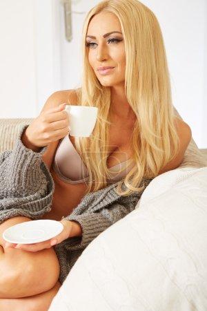 Femme souriante tenant une tasse de café