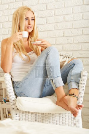 Photo for Beautiful elegant woman barefoot in blue jeans drinking coffee - Royalty Free Image