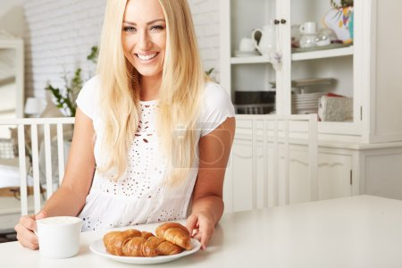 Photo for Beautiful young blonde woman enjoying a fresh crispy croissant and a mug of coffee for her breakfast - Royalty Free Image