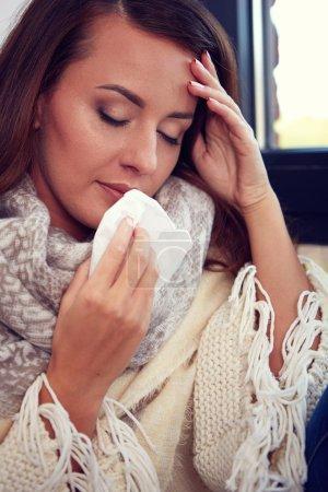 Photo pour Grippe. Image rapprochée d'une femme malade frustrée au nez rouge - image libre de droit