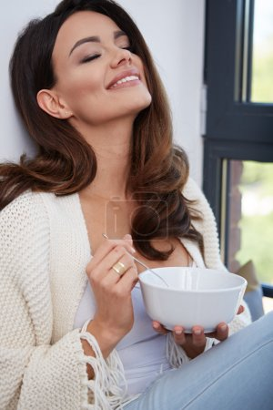 Photo for Young woman eating soup by the window. - Royalty Free Image