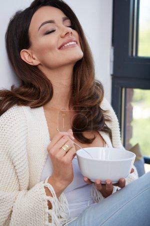 Photo pour Jeune femme mangeant soupe par la fenêtre. - image libre de droit
