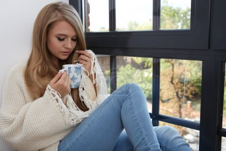 Photo for Young woman in a sweater by the window in a loft. - Royalty Free Image