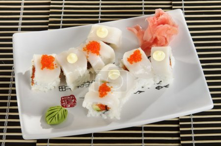Sushi menu: a set of rolls of scallops with wasabi and ginger on a plate