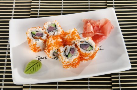 Sushi menu: a set of rolls with flying fish roe and avocado with wasabi and ginger on a plate