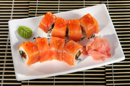 Sushi menu: a set of rolls of salmon and avocado with wasabi and ginger on a plate