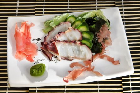 Sushi menu: sliced octopus with slices of cucumber and seaweed on a plate