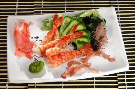 Sushi menu: shrimp with slices of cucumber and seaweed on a plate