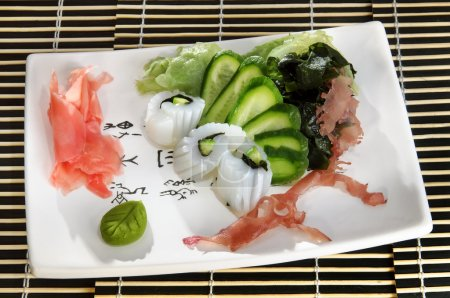 Sushi menu: shrimp with slices of cucumber and seaweed on a plate...