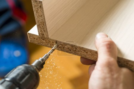 Furniture assembly. Master drills drill a hole in the furniture board.