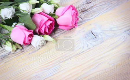 Photo for Pink roses and white flowers on a wooden background - Royalty Free Image