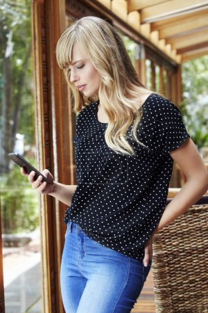 Blond young woman texting