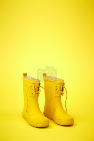Photo for Bright yellow boots in yellow studio - Royalty Free Image