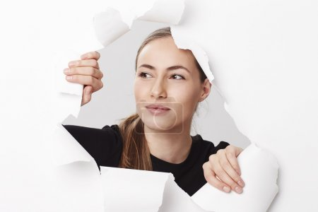 Photo pour Belle femme regardant à travers le papier déchiré - image libre de droit