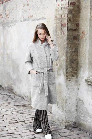 woman in grey coat on call