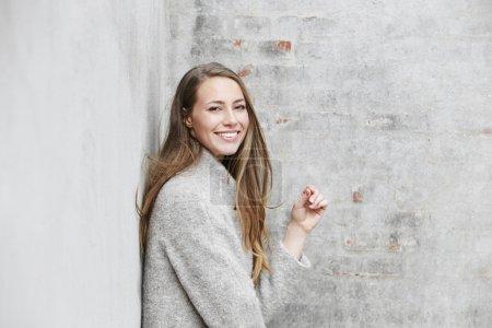 Photo pour Portrait de femme en mode gris contre mur - image libre de droit