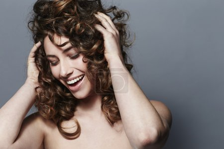 Young woman touching curls, smiling...