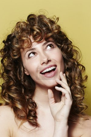 Photo for Happy young woman with curly hair, looking up - Royalty Free Image