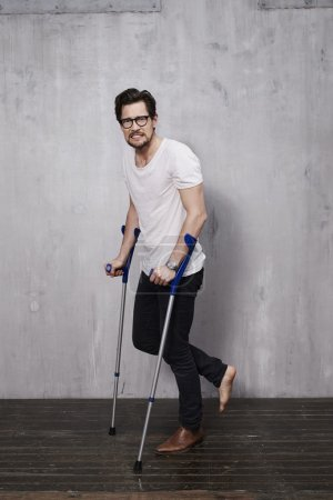 Photo for Anxious young man on crutches in studio - Royalty Free Image