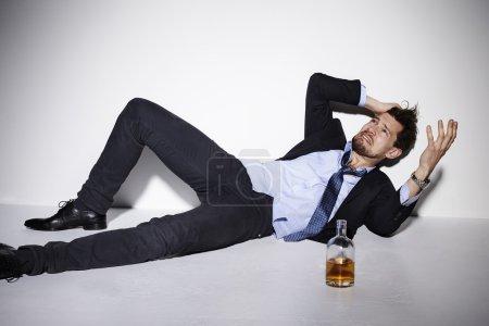 Photo pour Homme d'affaires désespéré ivre en studio - image libre de droit